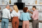 back view of men feeding mature women while standing together in kitchen
