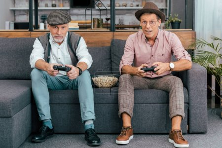 handsome mature men using joysticks and looking at camera while sitting together on couch
