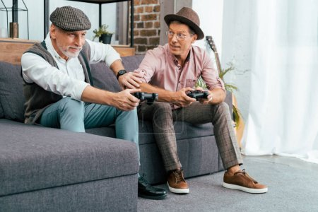 emotional mature male friends playing with joysticks at home
