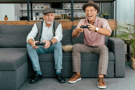 handsome mature men sitting on sofa and playing with joysticks
