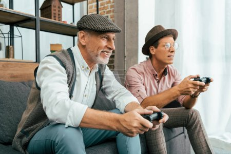 two mature male friends sitting on couch and playing with joysticks at home