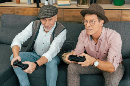 two mature male friends playing with joysticks at home