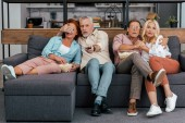 scared mature couples sitting on couch and watching tv together