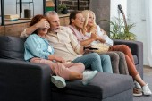 scared mature friends sitting on sofa and watching tv together at home