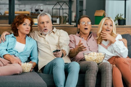 shocked mature friends sitting on couch and watching tv together