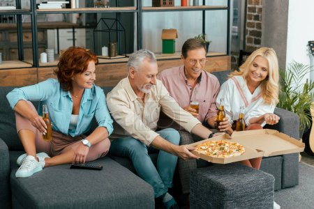 happy mature friends eating pizza and drinking beer while sitting on couch and spending time together at home