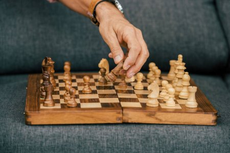 close-up partial view of man playing chess on couch