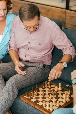 high angle view of mature man in eyeglasses playing chess with friends at home