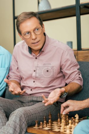 mature man in eyeglasses looking away and playing chess with friends