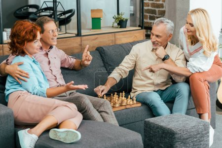 happy mature friends gathering together and playing chess at home