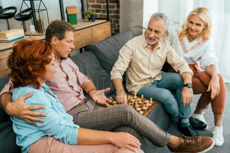 two mature couples sitting on couch and playing chess at home