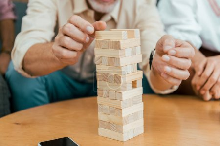 cropped shot of mature people playing with wooden blocks at home