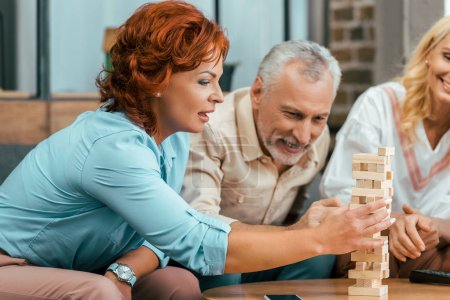 beautiful mature woman playing with wooden blocks while spending time with old friends at home