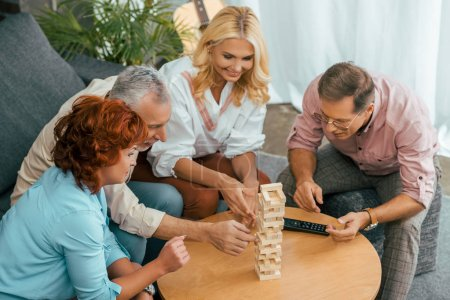 high angle view of smiling old friends building tower from wooden blocks on table