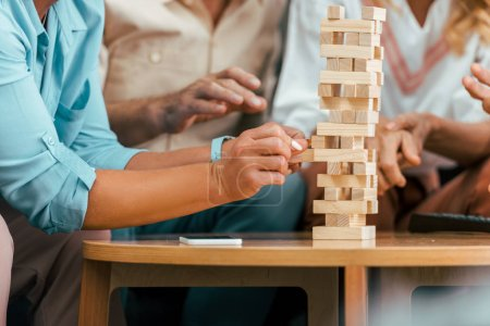 cropped shot of mature friends building tower from wooden blocks on table