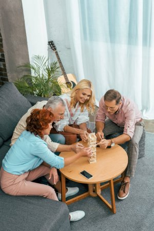 high angle view of happy mature friends playing with wooden blocks at home