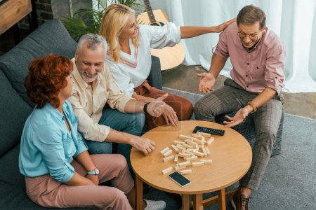 high angle view of smiling old friends playing with wooden blocks at home