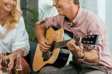 Photo for Cropped shot of mature man playing guitar and looking at beautiful smiling woman at home - Royalty Free Image