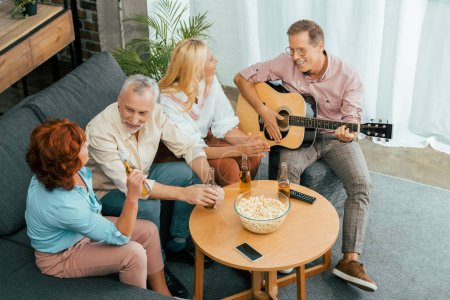 high angle view of happy mature friends spending time with guitar and beer at home