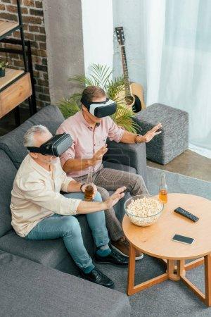 Foto de Vista de ángulo alto de hombres maduros bebiendo cerveza y usar auriculares de realidad virtual mientras está sentado en el sofá - Imagen libre de derechos