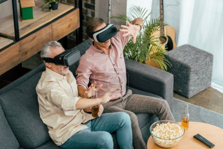 high angle view of mature men drinking beer and using virtual reality headsets at home