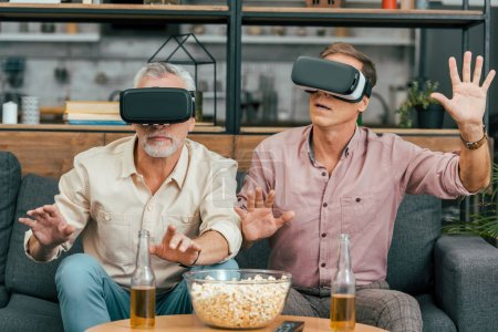 handsome mature male friends sitting on couch and using virtual reality headsets