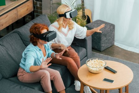 high angle view of mature female friends using virtual reality headsets at home