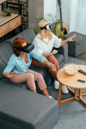high angle view of mature women using virtual reality headsets at home