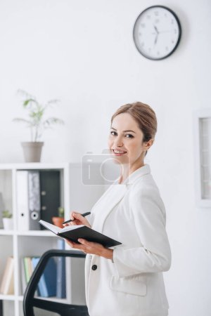 attractive smiling businesswoman working with planner in modern office