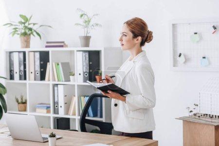 Photo pour Gestionnaire de confiant avec le planificateur de bureau moderne avec ordinateur portable - image libre de droit
