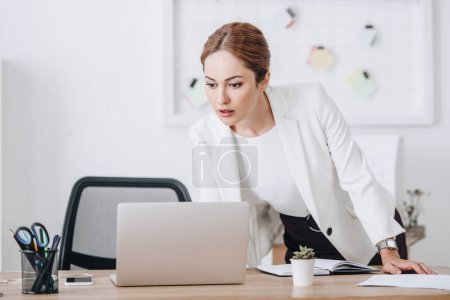businesswoman working with diary and laptop at workplace