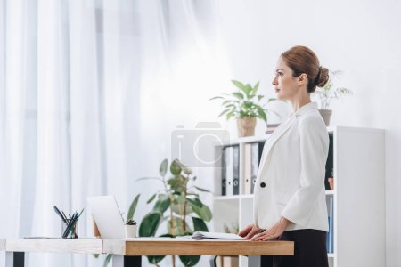 confident businesswoman working with diary and laptop at workplace