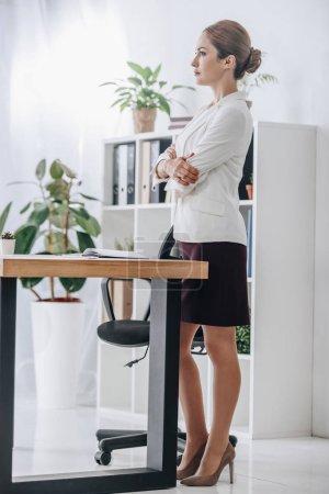 Photo pour Femme d'affaires confiant debout au tableau avec planificateur et ordinateur portable au bureau - image libre de droit
