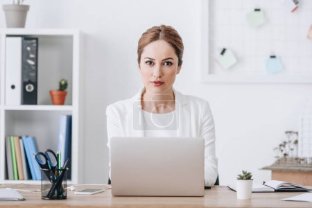 confident businesswoman in formal wear working with laptop in office