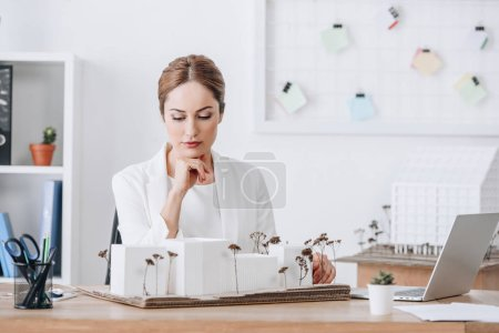 pensive female architect looking at house model in office