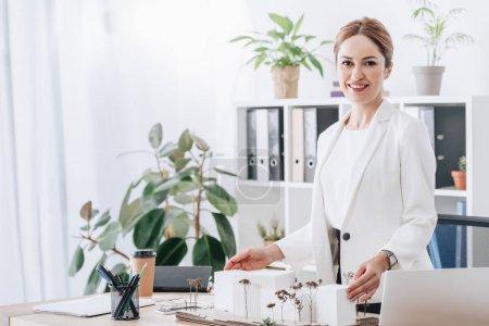 Foto de Sonriente a mujer arquitecto trabajando en oficina moderna con casa modelo - Imagen libre de derechos