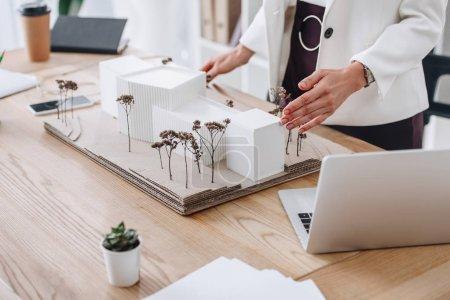 Photo pour Vue partielle de l'architecte professionnel travaillant avec le modèle de maison sur le lieu de travail - image libre de droit
