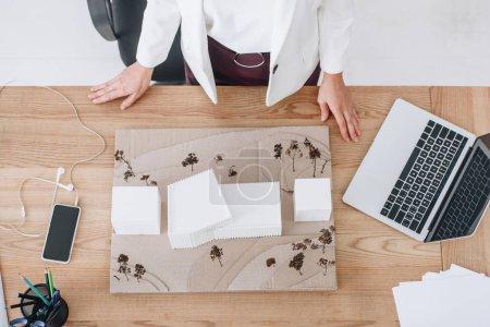 Photo pour Recadrée vue d'architecte travaillant avec la maison modèle au milieu de travail - image libre de droit