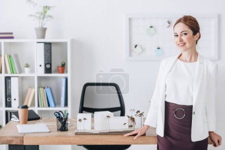 beautiful female architect posing at workplace with house model