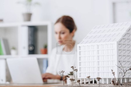 Photo for Selective focus of house model and architect working with laptop in office - Royalty Free Image