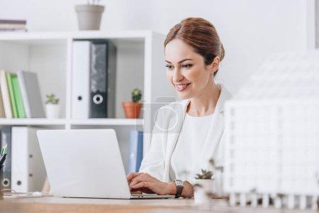 Foto de Sonriente a mujer arquitecto trabajando con el portátil en el lugar de trabajo con la casa modelo, enfoque selectivo - Imagen libre de derechos