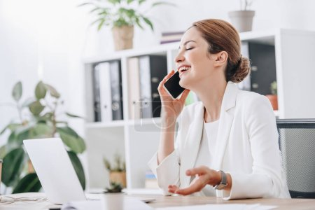 laughing businesswoman talking on smartphone in office with laptop