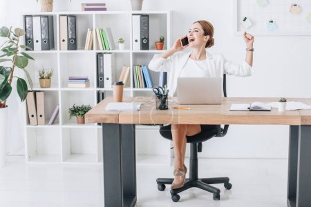 successful businesswoman talking on smartphone while triumphing in modern office with laptop