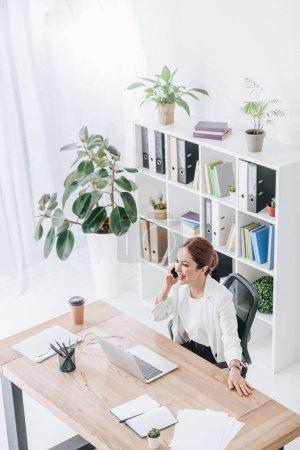 Photo pour Femme d'affaires gai parler sur smartphone moderne bureau avec ordinateur portable - image libre de droit