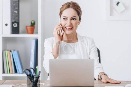 Erfolgreiche Geschäftsfrau spricht am Arbeitsplatz mit Smartphone und Laptop