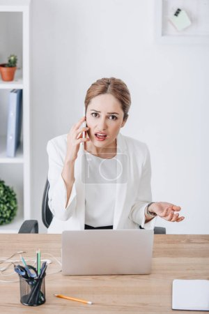 confused emotional businesswoman talking on smartphone at workplace with laptop