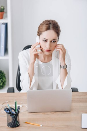stressed businesswoman talking on smartphone at workplace with laptop