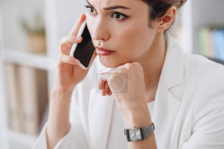 attractive worried businesswoman talking on smartphone in office