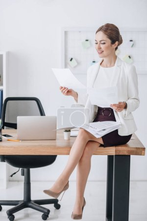 attractive professional business woman doing paperwork while sitting on table with laptop