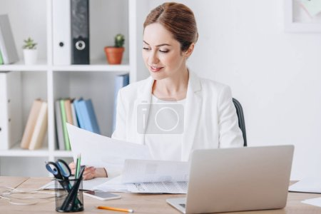 Photo for Beautiful executive businesswoman working with documents and laptop at workplace in modern office - Royalty Free Image